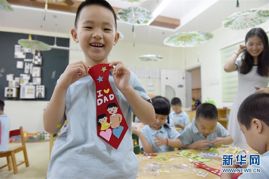 6月14日,合肥市经开区中环城幼儿园的一名小朋友展示自己制作的创意小领带。临近父亲节和端午节,安徽省合肥市经开区中环城幼儿园的小朋友们在老师的带领下,亲手制作送给父亲们的创意小领带和微型彩绘龙舟,表达对父亲感谢的同时了解中国传统节日。新华社记者 郭晨 摄